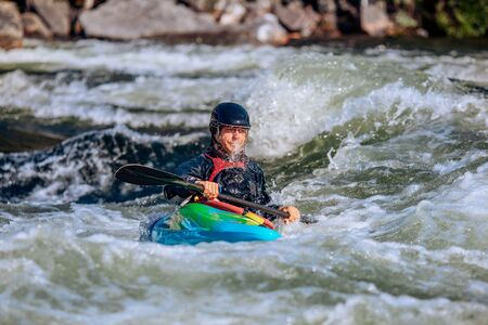 Guy in kayak sails mountain river. Whitewater kayaking, extreme sport rafting.