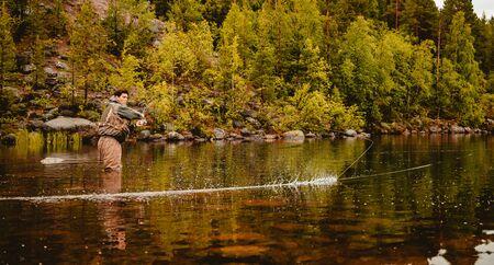 Fisherman using rod fly fishing in mountain river autumn splashing water.