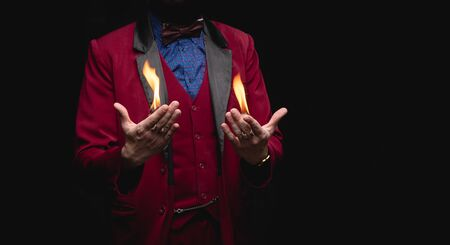 Magician shows trick with fire burn from palms hands.