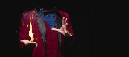 El mago muestra truco con quemadura de fuego de las palmas de las manos.