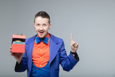 Children magician in blue suit holds gift box with gifts and points his finger copy space for text. New Year christmas concept