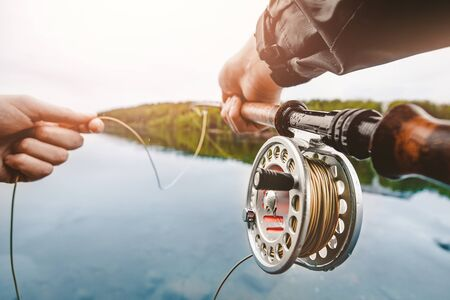 Coil of fly fishing rope, man hands holding rod.