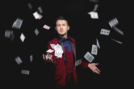 Illusionist magician man shows magic with playing cards on black background