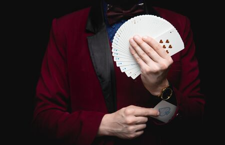 Illusionist man shows fan of playing cards takes ace out hand on black background. Reklamní fotografie
