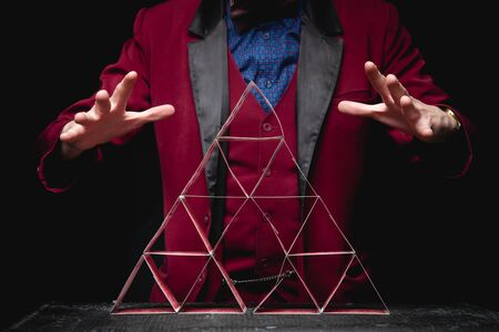Magician shows trick pyramid with playing cards on dark background. 写真素材