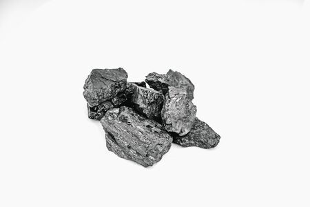Pieces black coal lie on white isolated background, copy space.