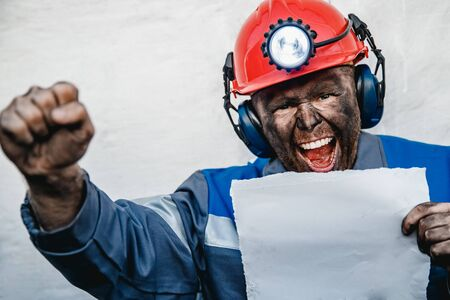 Miner angry man screams and frowns, holds sheet of paper for text. Concept mining strike uprising