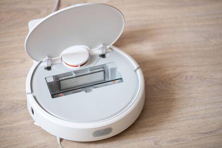 Open robotic wireless smart vacuum cleaner working on laminate flooring