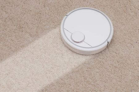 Robotic wireless smart vacuum cleaner working on white with pile carpet. Concept before and after service Stok Fotoğraf
