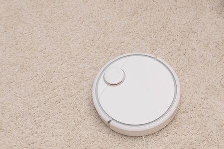 Robotic wireless smart vacuum cleaner working on white with pile carpet