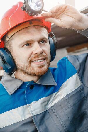 Concept industrial engineer. Portrait miner coal man in helmet with lantern in underground mine 写真素材