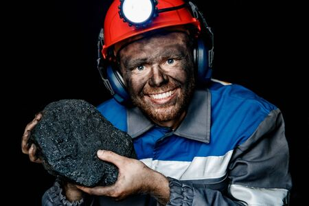 Miner dirty hands holding piece of coal mine