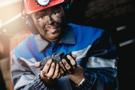 Miner happy man smiling after working on coal mine. Concept industrial engineer