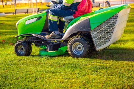 Gardener worker on lawn mower tractor cuts green grass.
