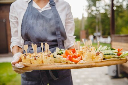 Catering service. Waiter man in apron carries food snacks on platter Stock fotó