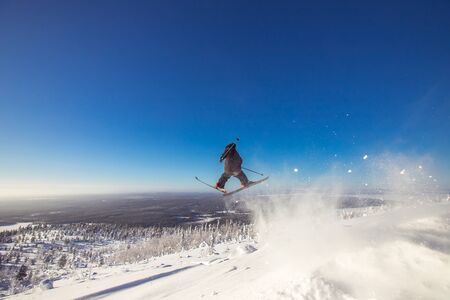 Skier jumps in fresh snow freeride in mountains against background forest Banque d'images - 132321220