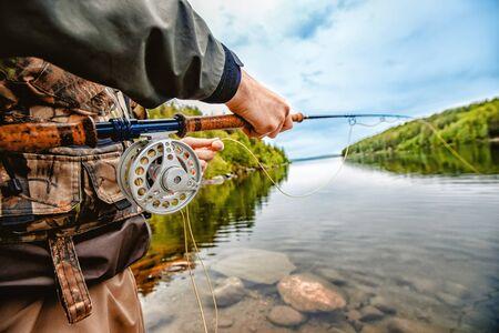 Pescador con caña de pescar con mosca en el río de la montaña