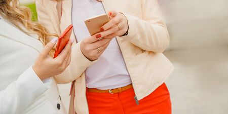 Young women girlfriend couple hold phones with hands. Network messengers concept