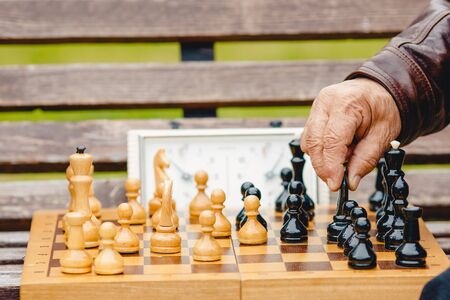 Elderly man senior holds chess piece game board outdoors Stok Fotoğraf