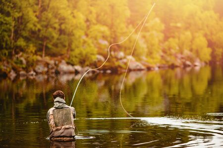 Fisherman using rod fly fishing in mountain river autumn splashing water.