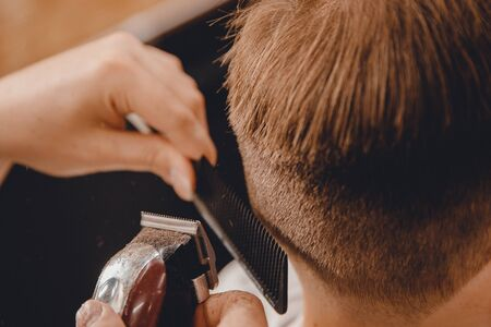 Barber master hairdresser does hairstyle scissors and comb. Concept Barbershop