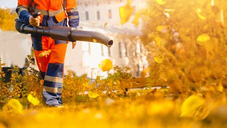 Male worker removes leaf blower leaves lawn of garden Autumn.