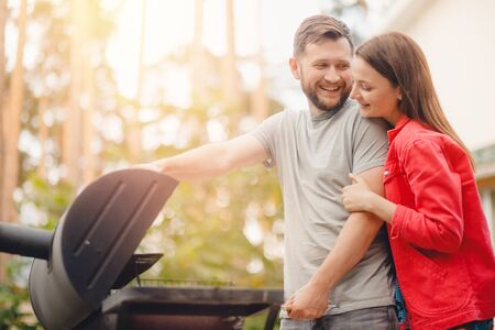 Happy Man and young woman fries meat on BBQ grill in nature garden