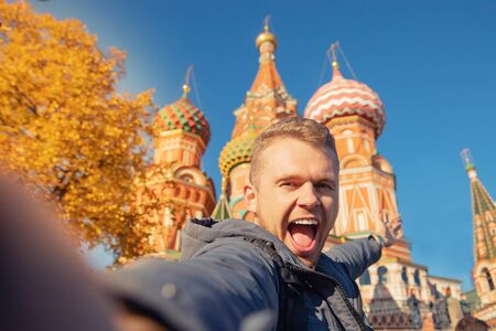 Male tourist makes selfie photo on background Saint Basil Cathedral Red Square in Moscow, Russia autumn. Travel concept Imagens
