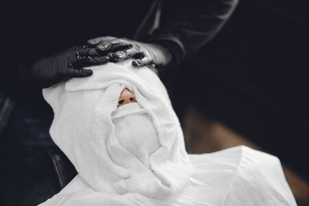 Barber steam face skin of man with hot towel before royal shave in Barbershop.