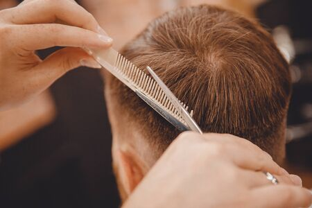 Barber master hairdresser does hairstyle with scissors and comb. Concept Barbershop Standard-Bild