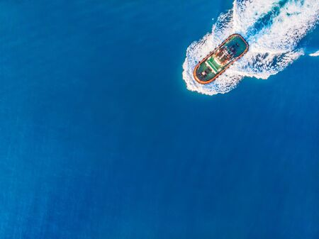 Tugboat sails to meet liner or cargo ship in port. Top view of blue ocean. Archivio Fotografico