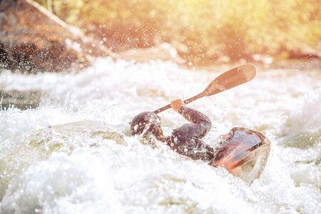 Whitewater kayaking, extreme sport rafting. Guy in kayak sails mountain river. Stock Photo