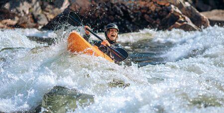 Guy in kayak sails mountain river. Whitewater kayaking, extreme sport rafting.