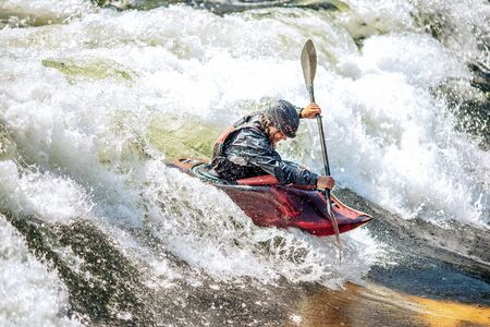 Whitewater kayaking, extreme sport rafting. Guy in kayak sails mountain river. Stock Photo