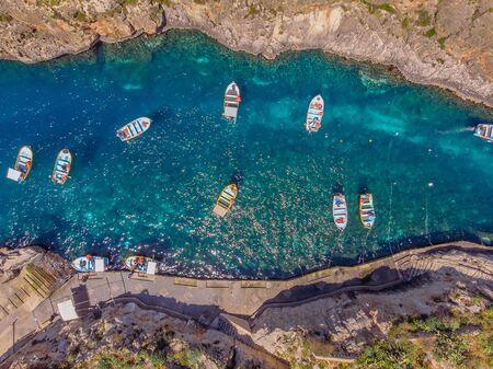 Blue Grotto in Malta. Pleasure boat with tourists runs. Aerial top view.