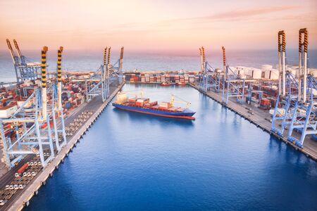 Großes Containerschiff verlässt Frachthafen auf See, Sonnenuntergang. Luftaufnahme von oben Standard-Bild