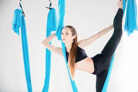 Aerial fly yoga in white gym, young gymnastics women in blue hammock 스톡 콘텐츠