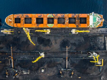 Loading coal Anthracite on bulk vessel ship in offshore cargo port. Aerial top view 版權商用圖片