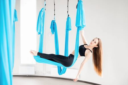 Young woman performing antigravity aerial yoga exercise in white studio
