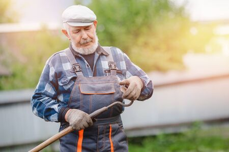 Elderly man senior is preparing tool for removing weeds in garden. Concept farmer agriculture. Stock fotó - 133397409