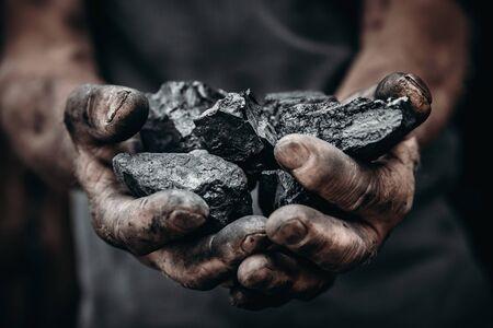 Coal in miner hands. Concept industry mining 写真素材