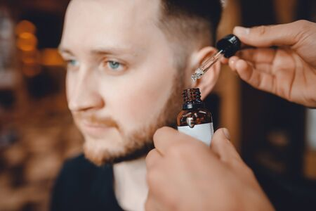 Barber does oil for care and growth of beard, barbershop