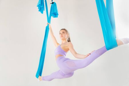 Hatha aero fly yoga concept. Beautiful young female trainer showing stretching exercises on blue hammock in white studio