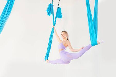 Aero fly yoga beautiful woman in uniform trainer shows asana stretching on blue hammock in white class 版權商用圖片