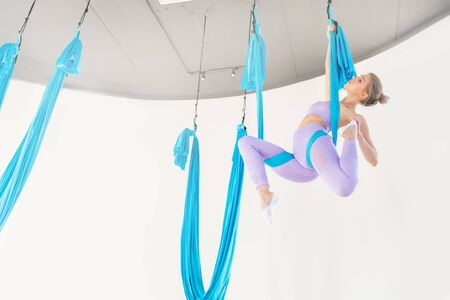 Beautiful young woman in uniform trainer shows asana stretching aero fly yoga on blue hammock in white class