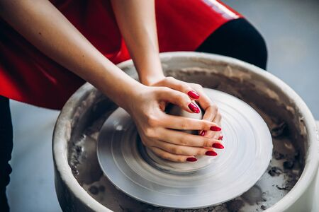Hands of woman make clay dishes on potter wheel, Top view. Concept elegance