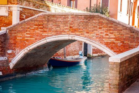 Bridge over canal for gondolas and boats in old city of Venice, Italy 写真素材