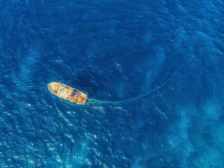 Fishing boat in blue sea water, fishermen set nets for fish. Aerial top view. 版權商用圖片