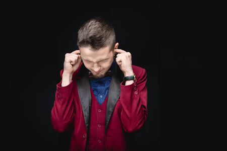 Man in red jacket covers ears with fingers, concept of lie, provocation, fatigue from people