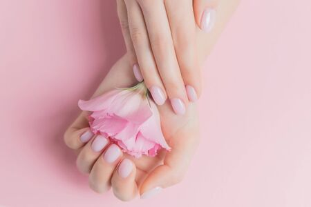 Beautiful stylish trendy female pink manicure with flower on background, top view. Concept beauty
